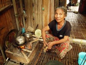 Seorang perempuan renta sedang menanak nasi di dalam gubuknya